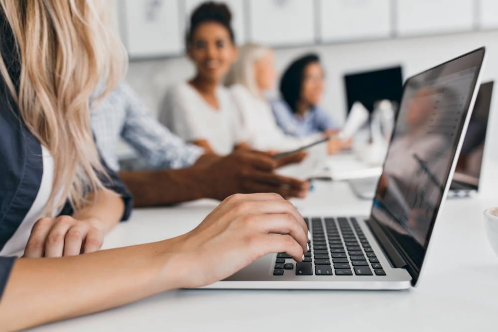 Slika plave devojke za laptopom u kancelariji