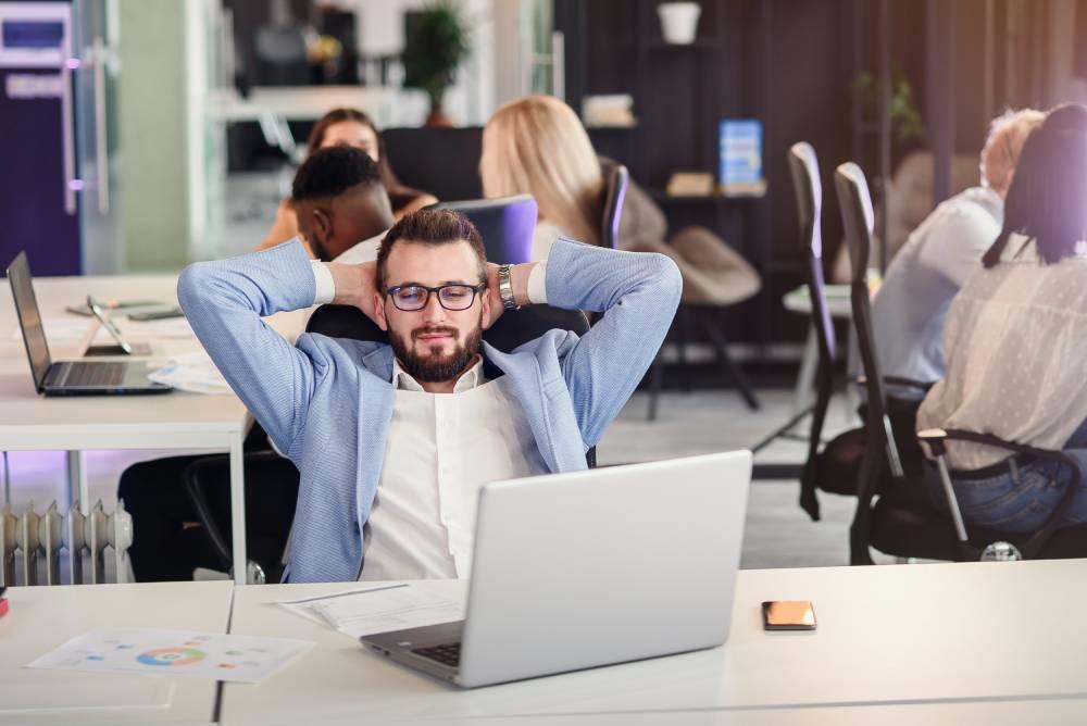 Čovek u svetloplavom sakou sedi u fotelji sa rukama iza glave i gleda u laptop