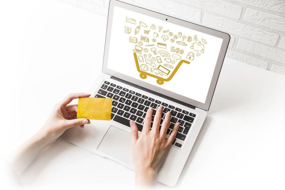 slika osobe za laptopom gde u jednoj ruci drži kreditnu karticu a drugom rukom pretražuje internetom