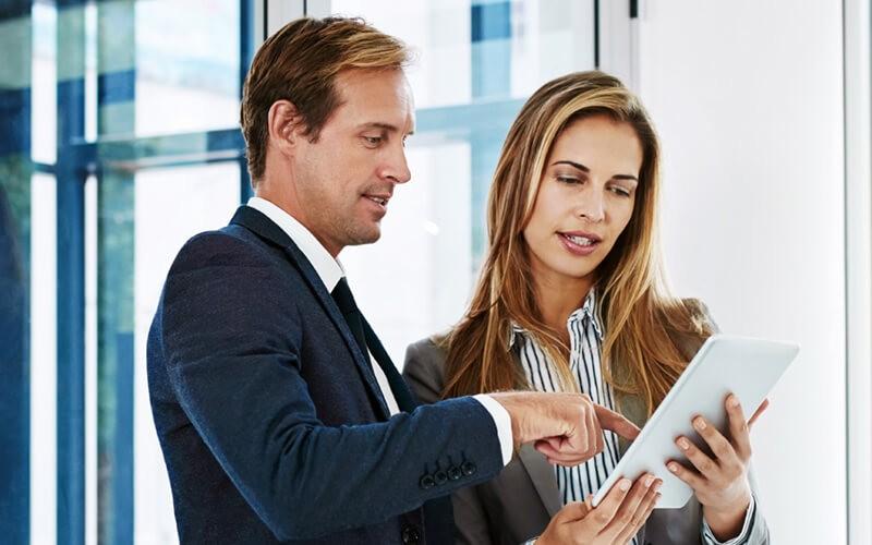 Čovek i žena u kancelariji gledaju izveštaje sap s4-hana managed cloud usluga na tabletu