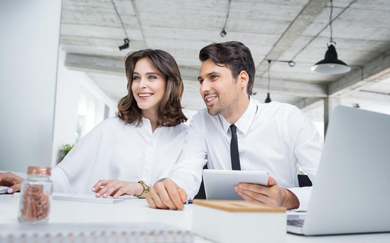 Slika muške i ženske osobe u kancelariji koji se smeju jer koriste Coming Managed cloud usluge