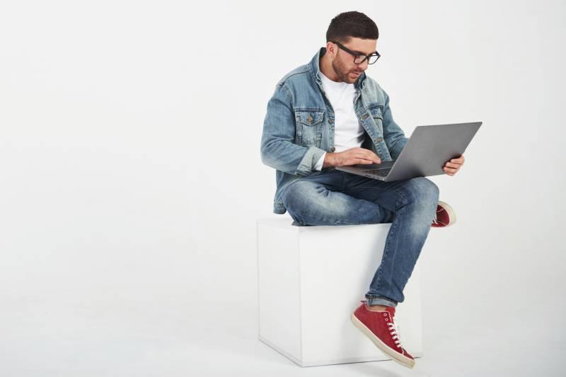 Programer za laptopom sedi na beloj kutiji