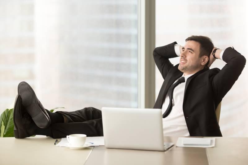 Čovek u odelu u kancelariji sa rukama iza glave i nogama na stolu uživa jer ima opciju remote backupa virtuelnih servera