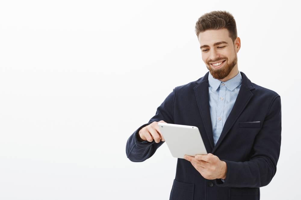 Čovek u odelu nasmejan na tabletu koristi tps cloud coming aplikaciju