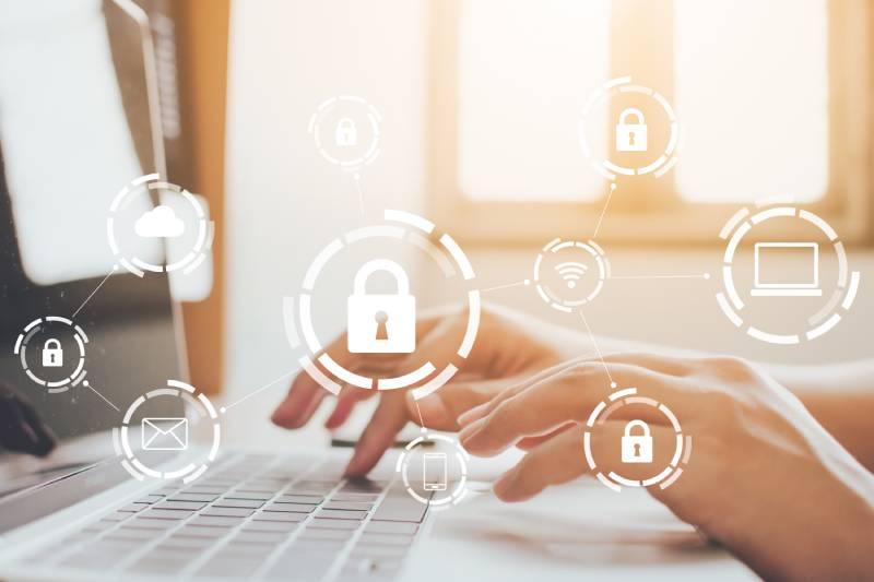 Slika osobe za laptopom i ilustracije katanaca koje predstavljaju vid online zaštite