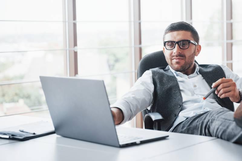 Poslovni čovek koji u kancelariji opušten za laptopom radi remote backup virtuelnih servera